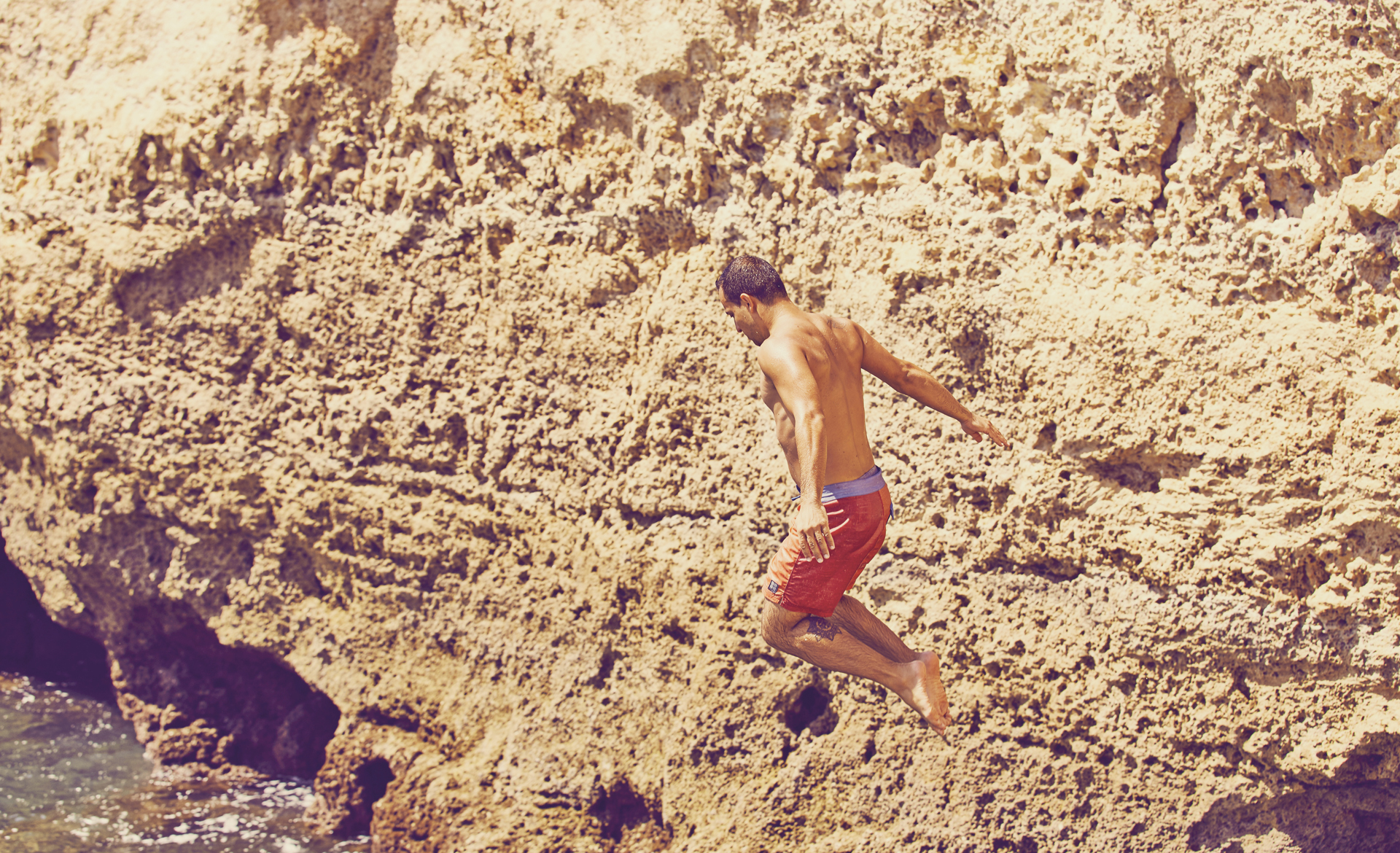 Mid air shot of a cliff jumper in Portugal