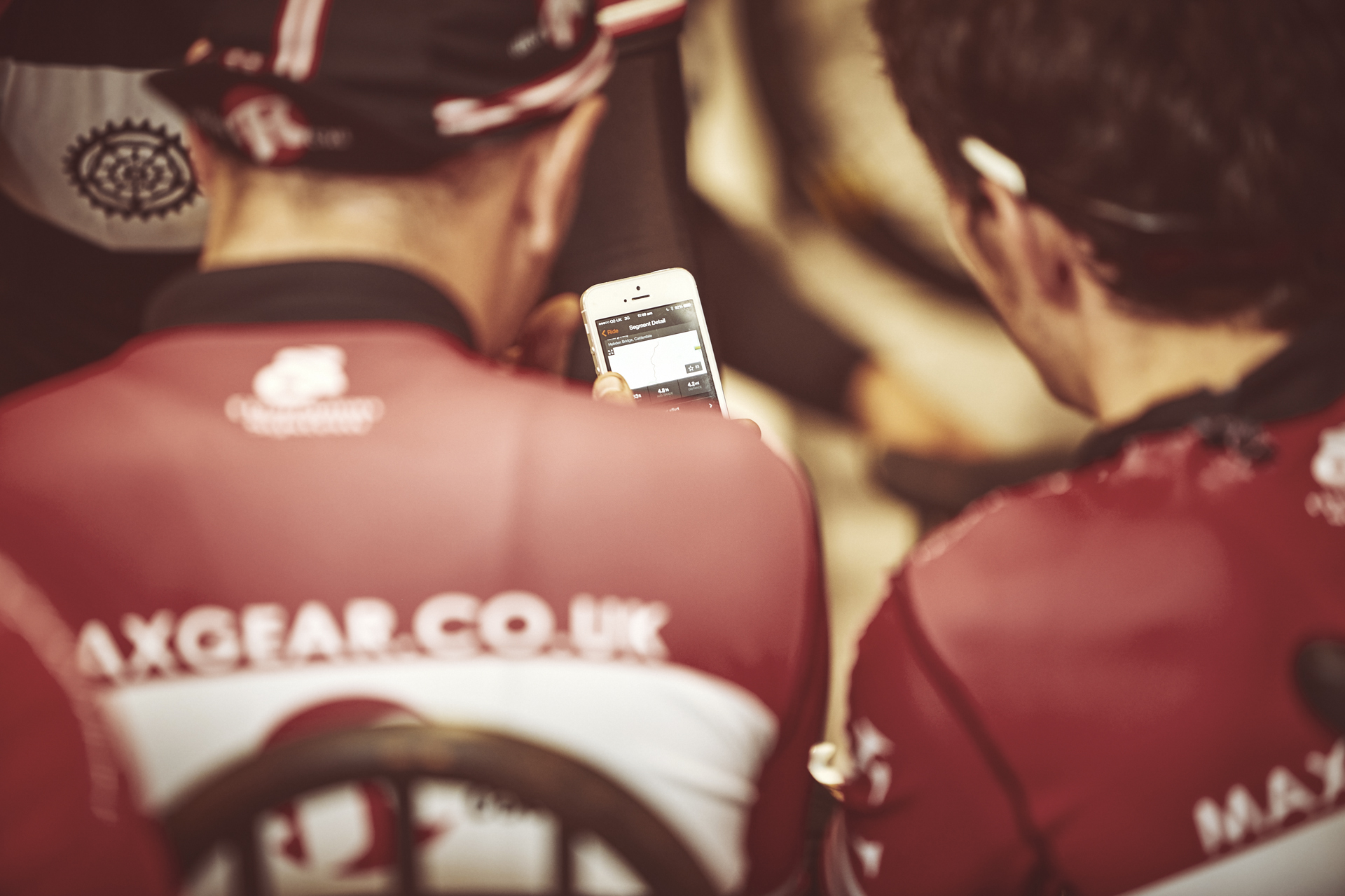 Cyclists looking at Strava on a mobile phone
