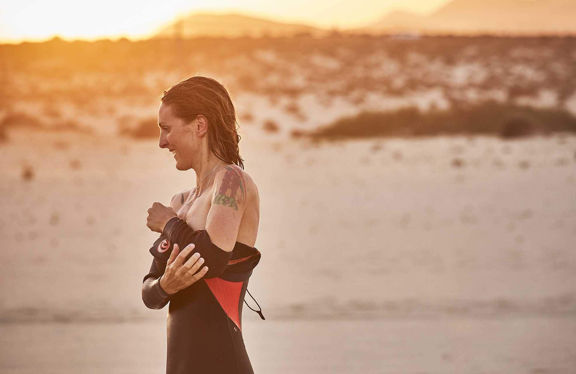 female surfer taking wetsuit off at sunset