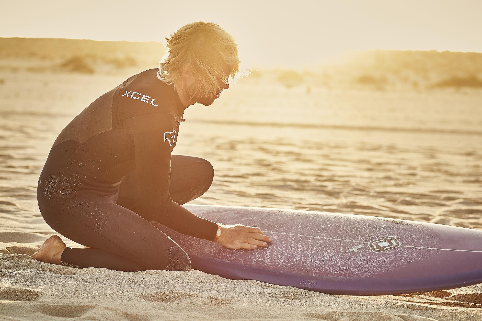 male surfer waxing his board