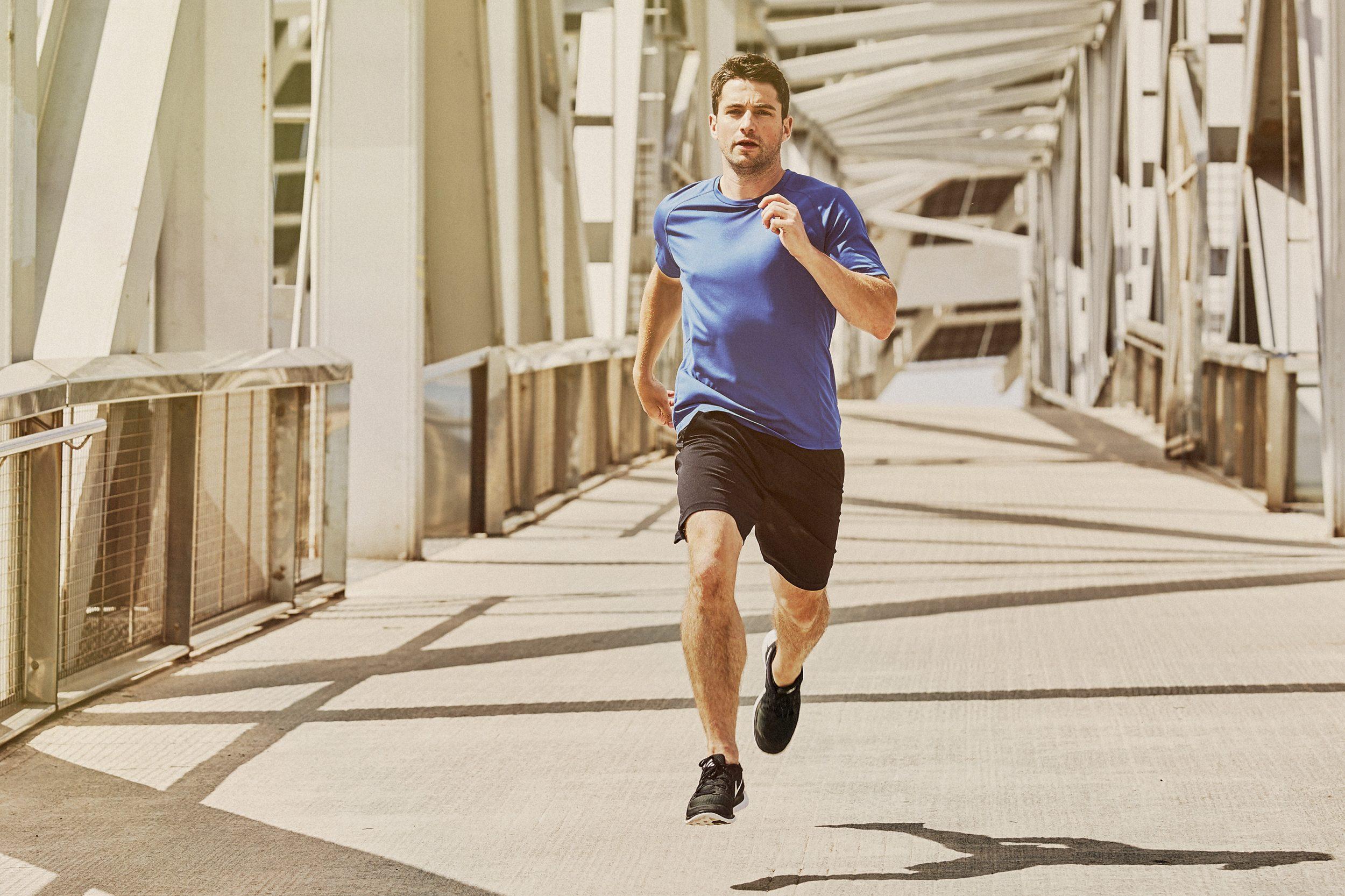 athlete running across a bridge