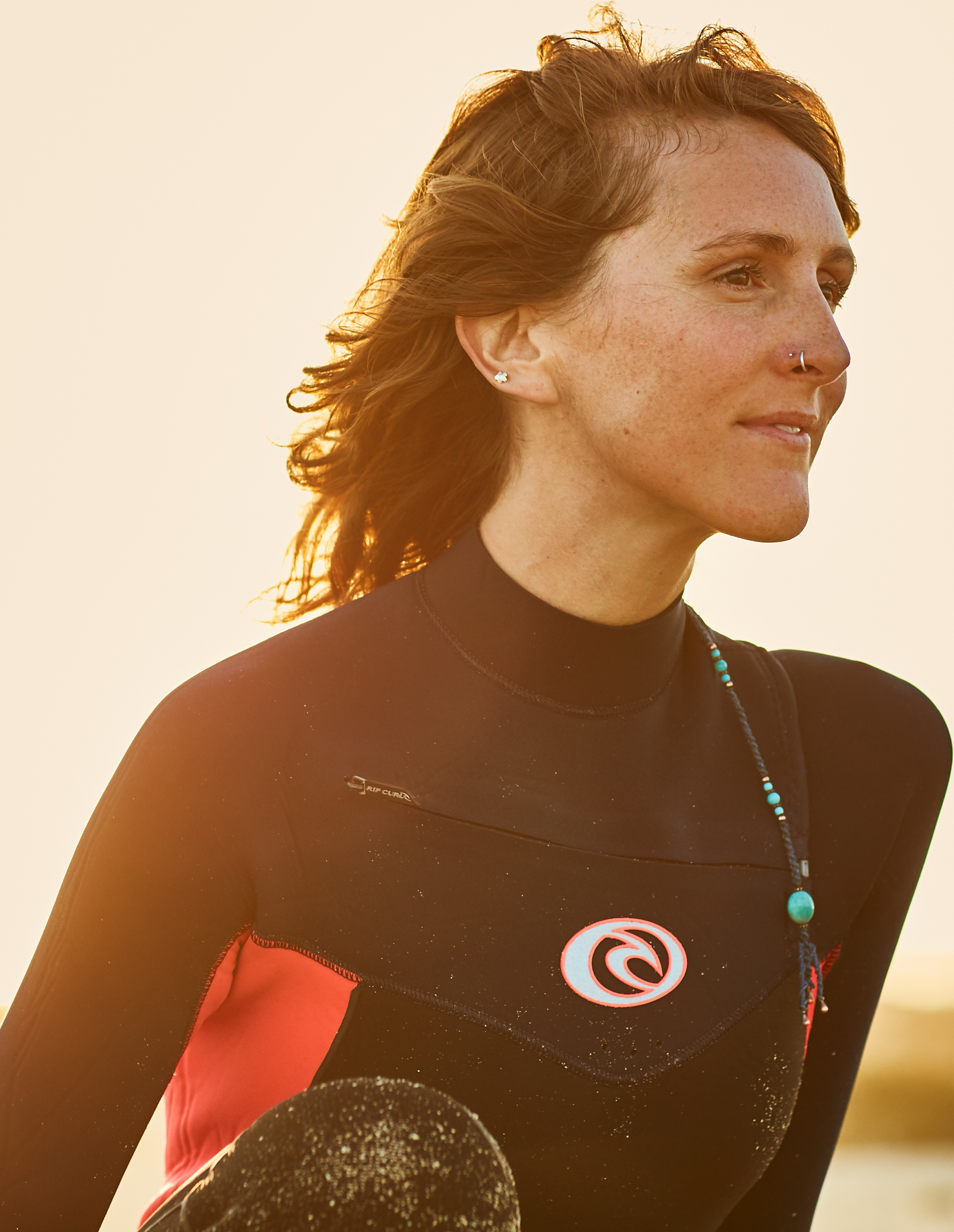 female surfer checks out the waves at sunset