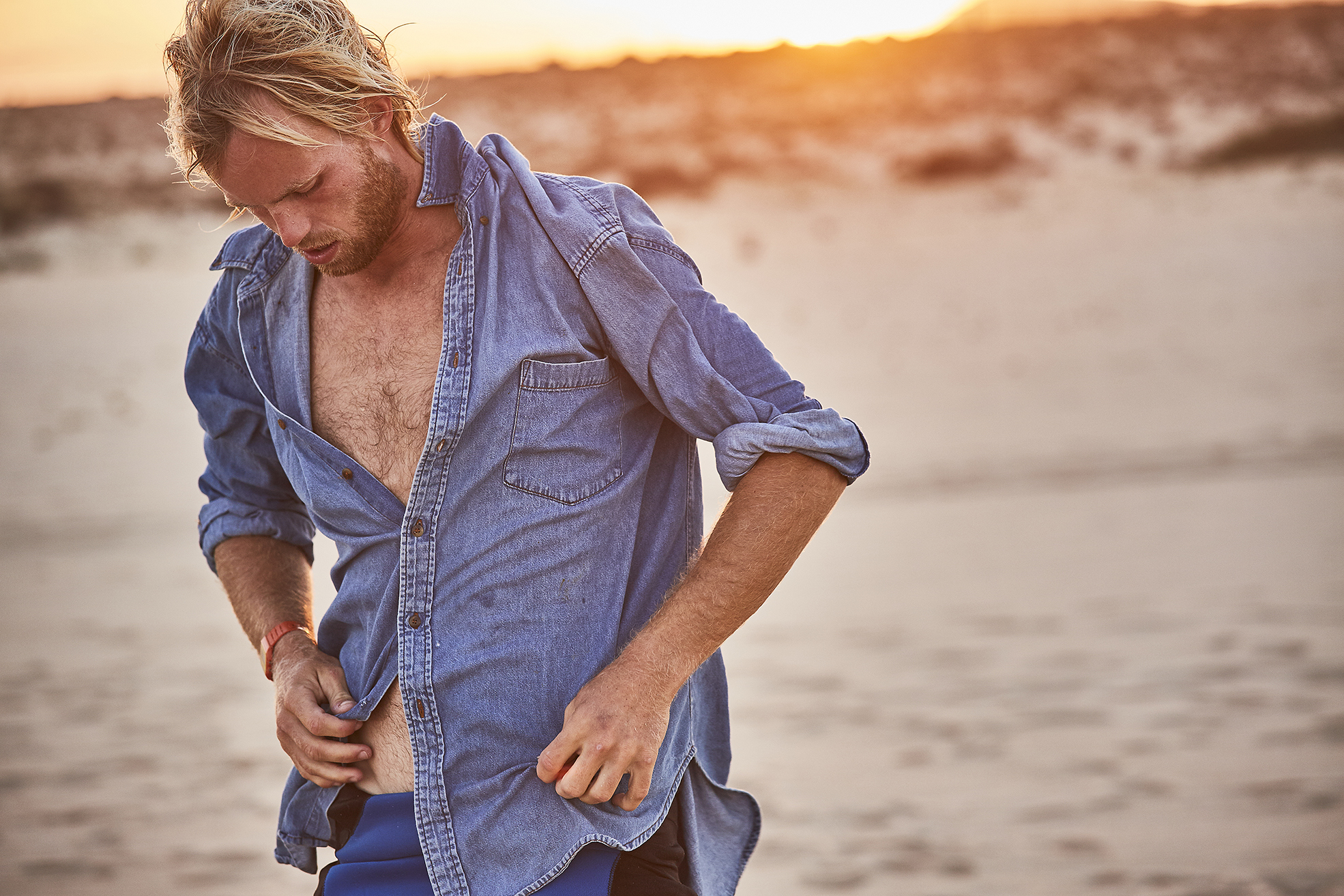 Surfer getting dressed after a sunset surf