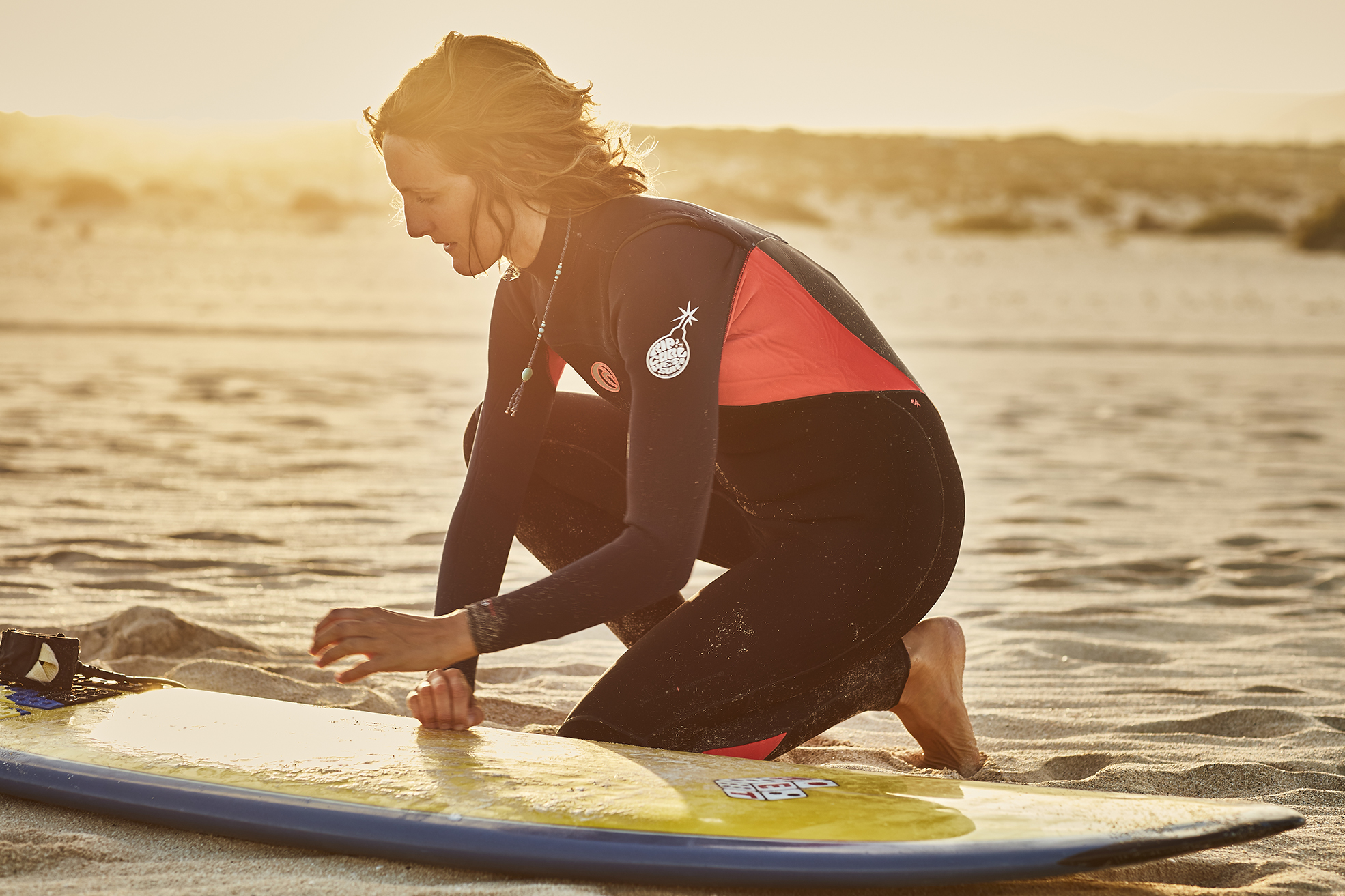 female surfer waxing her board at sunset