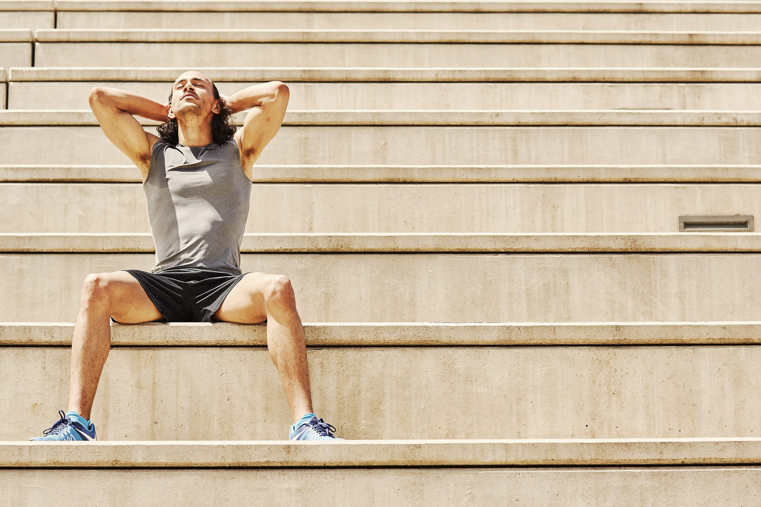 athlete resting on stairs after workout