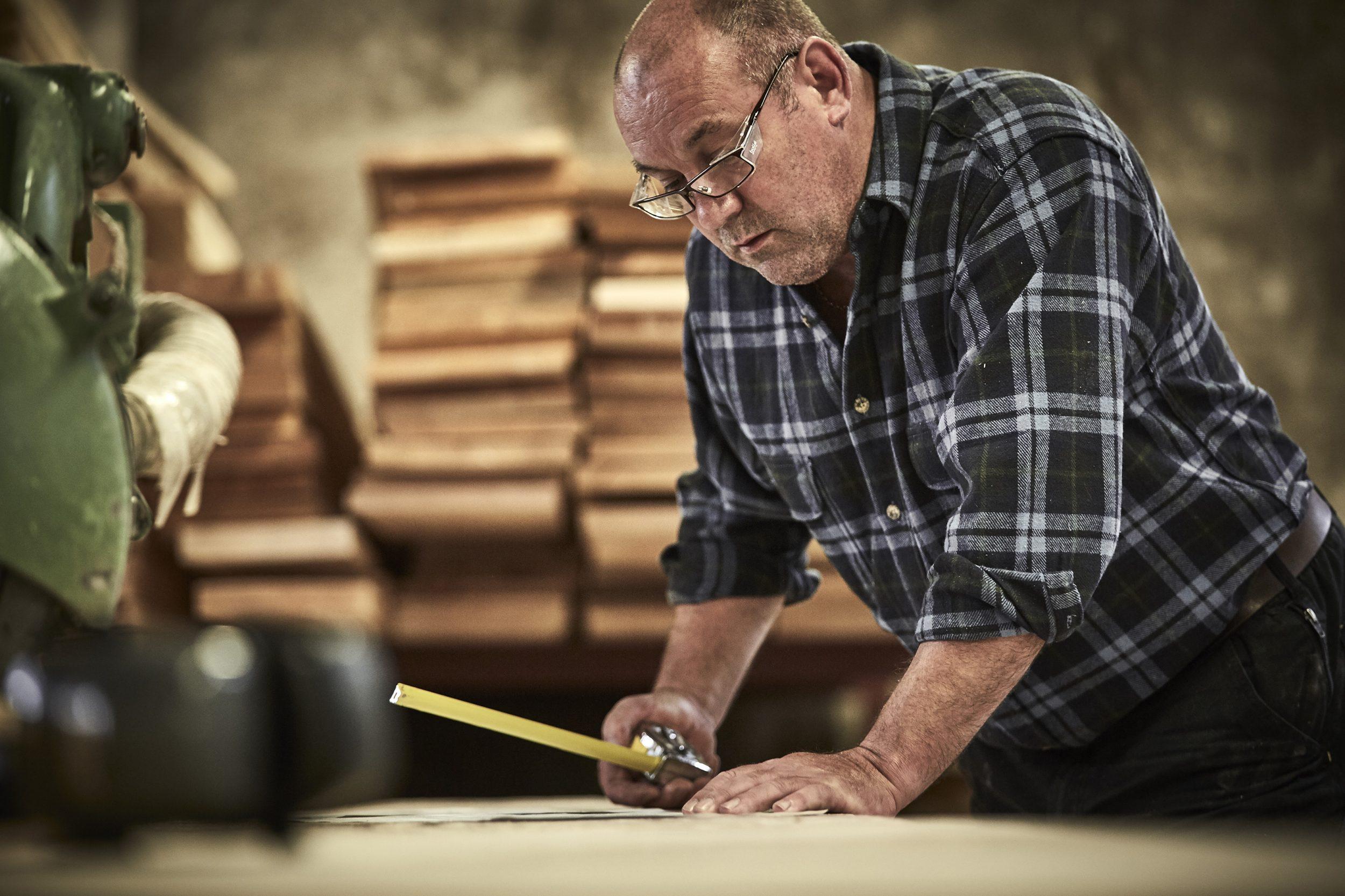 artisan measuring a length of wood
